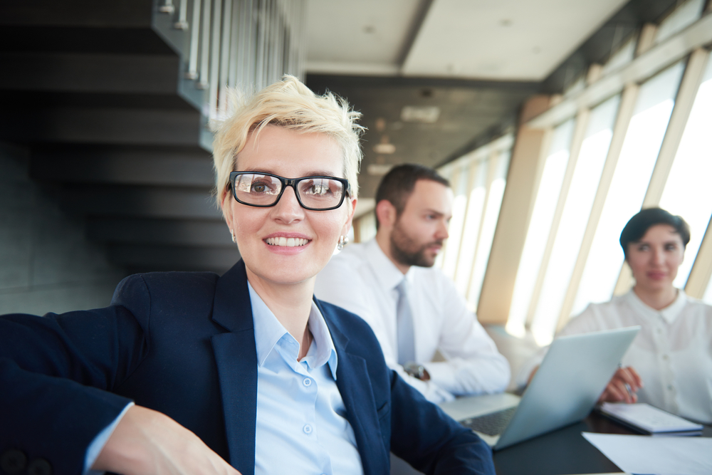 blonde with short hairstyle  and glasses,  business woman on meeting, people group in background at modern bright office indoors